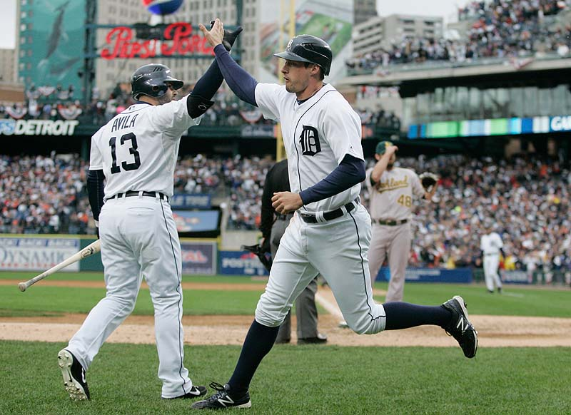 Don Kelly, right, is met at the dugout by Alex Avila after scoring on a wild pitch in the eighth inning for the Tigers in Game 2 of the American League division series on Sunday in Detroit. Kelly drove in the winning run in the ninth with a sacrifice fly to give Detroit a 2-0 series lead.
