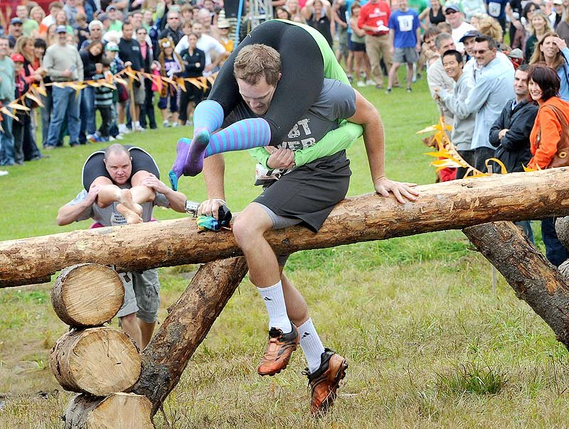 Brendan Doherty and Lauren McMillan from Brookline, Mass., lead Jim and Tanya Watson from South Portland over the first obstacle during the 13th annual North American Wife-Carrying Championship at Sunday River in Newry on Saturday.