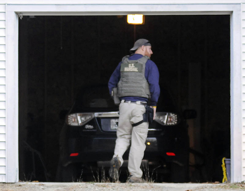 A U.S. Marshals Service investigator searches the garage at the residence of Barbara Cameron, the ex-wife of fugitive James Cameron, Tuesday in Hallowell. Authorities are continuing to hunt for Maine's former top drug prosecutor.
