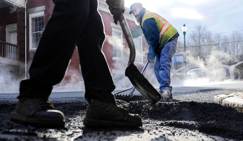 Ferraiolo Construction Co. workers Mark Megill, right, and Dave Buzzell spread pavement Monday on Church Street in Gardiner. The road received a new layer ahead of winter, as temperatures hovered below freezing.