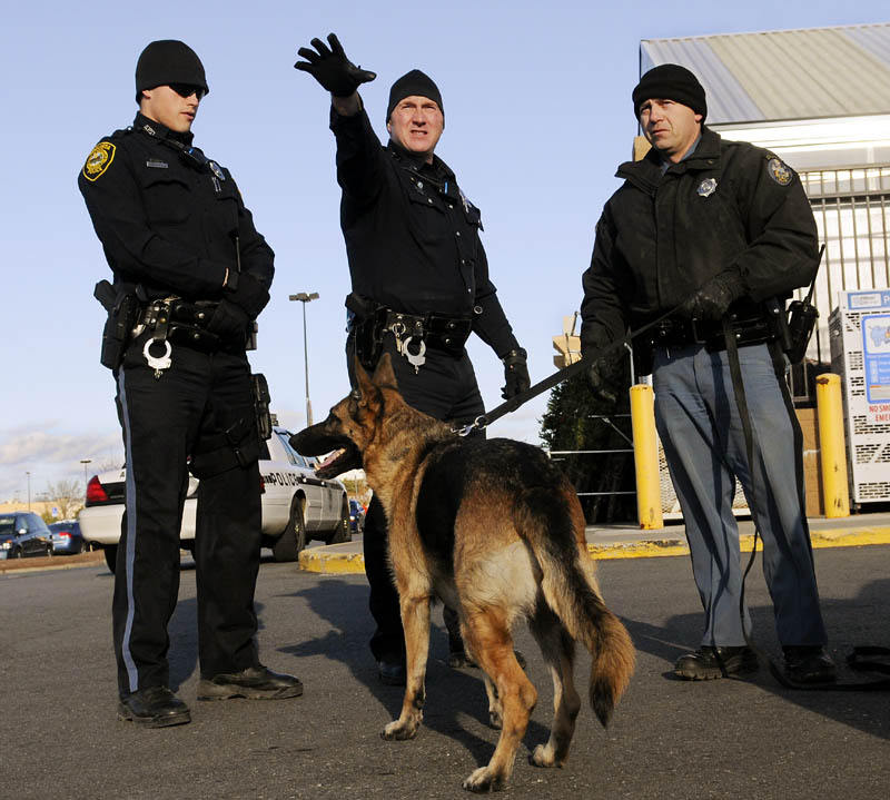 Augusta Police officer Niko Hample, left, and Sgt. Daniel Boivin, center, confer with State Trooper Rick Moody as they prepare to track a man who robbed the pharmacy of the Walmart in Augusta on Monday. Police followed a tracking dog who picked up the scent of the robber, who fled with drugs toward Civic Center Drive.