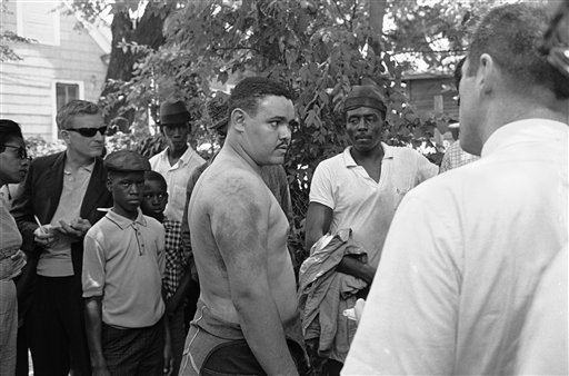 In this June 14, 1963, photo, Lawrence Guyot, 23, removes his shirt in Jackson, Miss., to show newsmen where he says Greenwood and Winona police beat him with leather slapsticks.