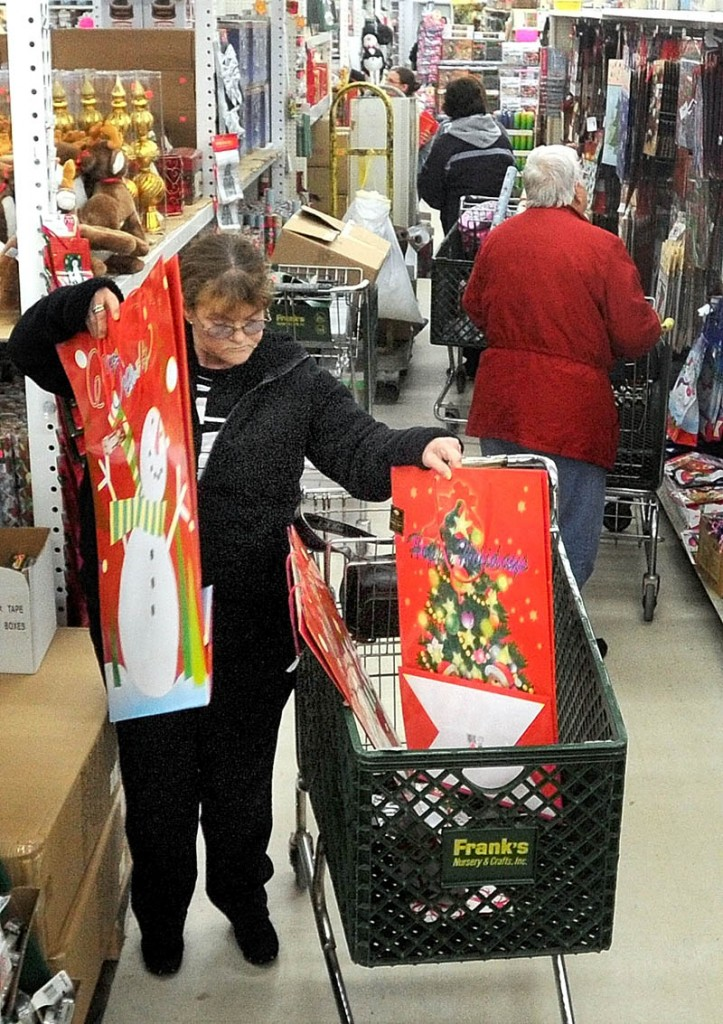 Dottie Currier, of Winslow, fills her cart with gifts packaging while shopping at Mardens Surplus and Salvage on Kennedy Memorial Drive in Waterville on Black Friday. Currier finished her shopping for her granddaughter and is focusing on finding gifts for her girlfriends for the remainder of the afternoon.