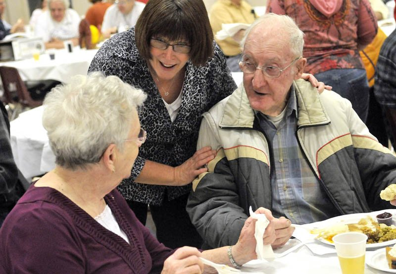 Volunteer Patsy Belanger, center, takes a moment to say hello to Sadie and Charlie Sturtevant, at the 23rd annual community Thanksgiving Day dinner at Messalonskee High School in Oakland, on Thursday.