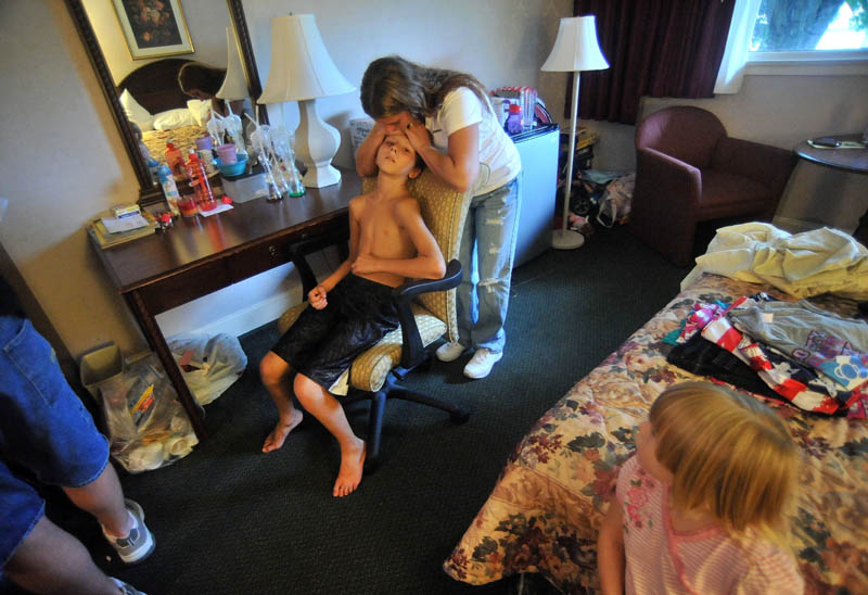 Janet White comforts her son, Dakota LaBrie, 11, in the hotel room that has been serving as home. The Whites had very little money at the time of the fire that destroyed their home, so extended periods of time in a hotel has been very costly.