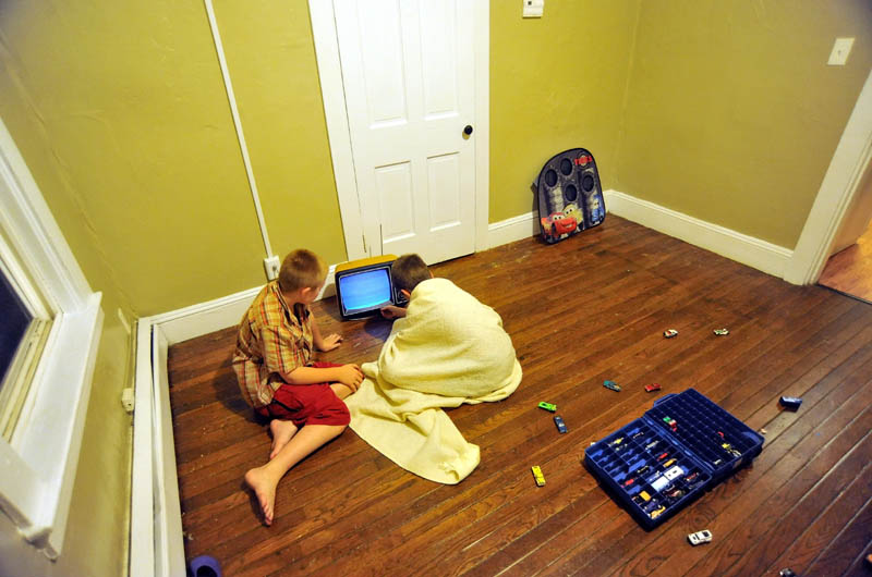 Raymond and Dakota LaBrie sit on the floor and try to get a donated, 12-inch, black-and-white television to work, on their first night in the family's new apartment on King Street in Waterville. According to their mother, Janet White, this is the first time the children have had their own rooms to sleep in, a positive side to the family's displacement by a fire that destroyed their Waterville home.
