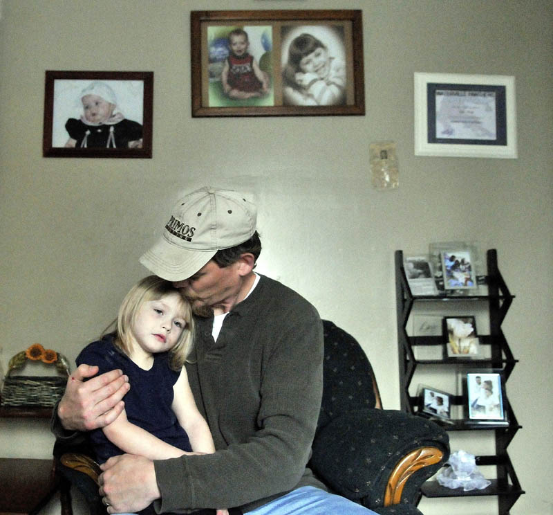 Jeff White gives his step-daughter, Savannah LaBrie, 4, a hug at the family's apartment on King Street in Waterville.
