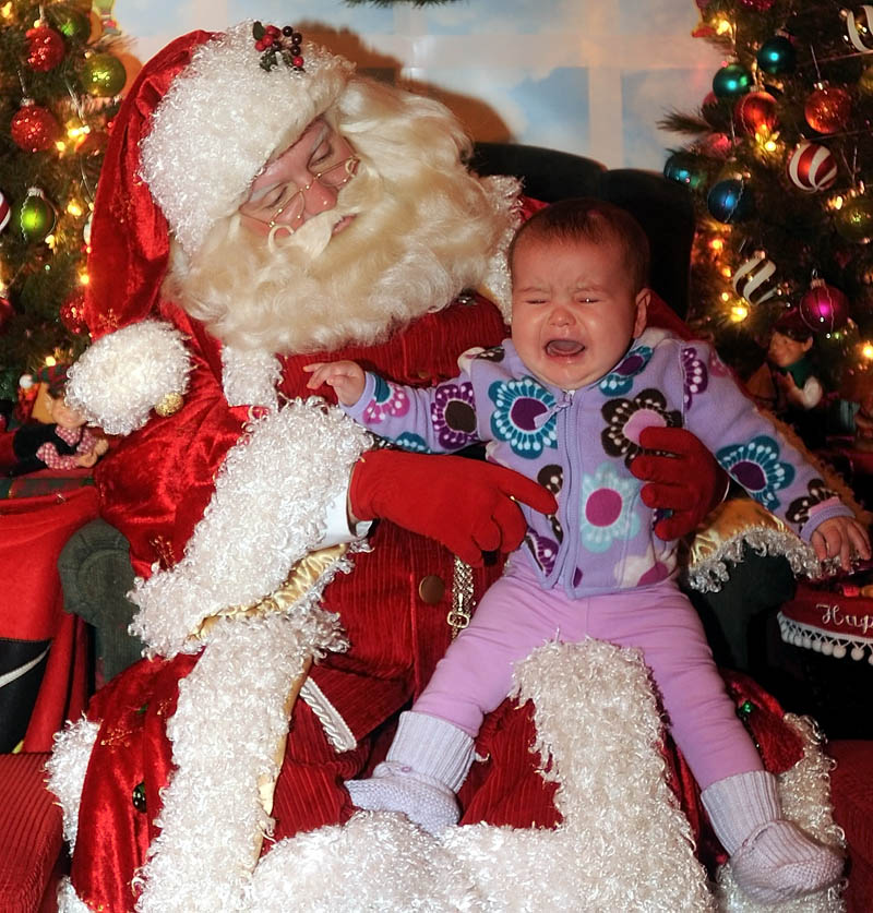 Avery Rodrigue, 7 months, of Saritoga, N.Y., cries as he sits on Santa Claus's lap at Kringleville, in Castonguay Square in downtown Waterville, on Saturday.