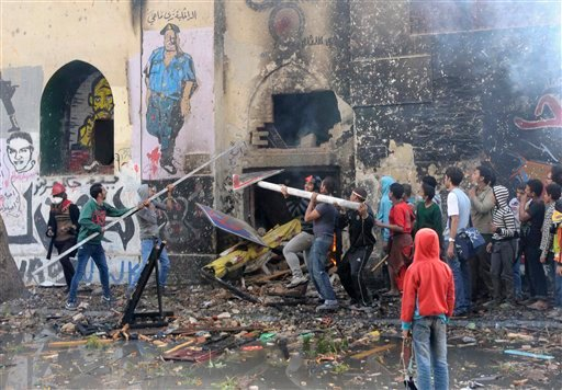 Egyptian protesters opposed to President Mohammed Morsi try to breach a building used by Morsi supporters during clashes near Tahrir Square in Cairo on Friday.