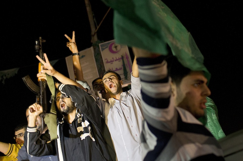 Palestinians celebrate the announcement of a cease-fire between Hamas and Israel in Gaza City, Wednesday, Nov. 21, 2012. Israel and the Hamas militant group agreed to a cease-fire Wednesday to end eight days of the fiercest fighting in nearly four years, promising to halt attacks on each other and ease an Israeli blockade constricting the Gaza Strip. (AP Photo/Bernat Armangue)