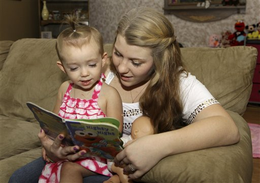 Kali Gonzalez reads to her daughter Kiah, 2, at their home in St. Augustine, Fla., recently. A new report by the National Women's Law Center says offering pregnant teens extra support would ultimately save taxpayers money by helping them become financially independent and not dependent on welfare.