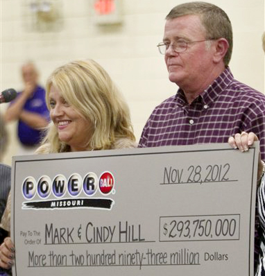 Cindy and Mark Hill hold a celebratory check for having one of the two winning Powerball tickets in Dearborn, Mo., on Friday.