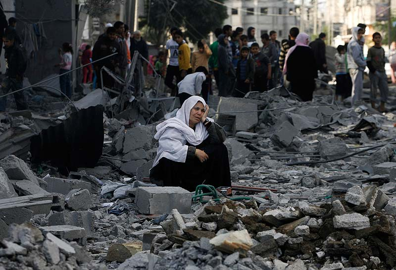 A Palestinian woman sits in rubble following an Israeli airstrike in Rafah refugee camp in southern Gaza Strip on Sunday. An Israeli envoy held talks with Egyptian officials Sunday on a ceasefire in his country's offensive on Gaza as Israel widened the range of its targets, striking more than a dozen homes of Hamas militants and two media officials.