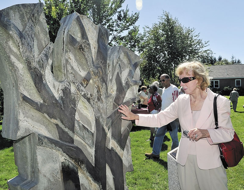 "WORK OF ART: Moira Fuller reaches out to touch a smooth portion of ""The Storm"" after the sculpture was unveiled during a ceremony at the Viles Arboretum in Augusta. It was sculpted by William Royall and was a gift from Elsie Pike Viles in memory of her late husband William Payson Viles. There are plans to bring in more art to the Arboretum so the public has a place to view art for free outdoors."