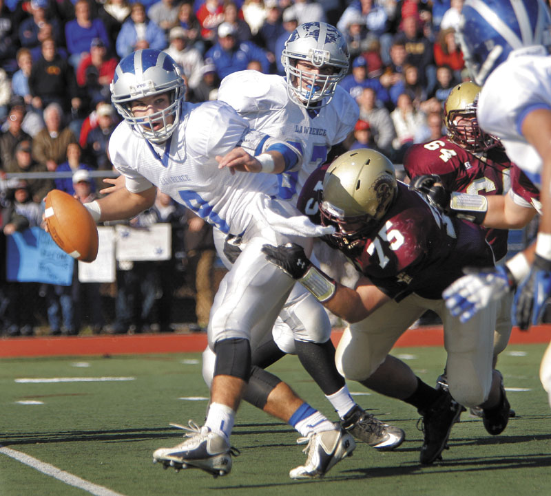 Spencer Carey of Lawrence looks for someone to pass to as he is brought down by Michael Granger of Thornton Academy in the Class A state football championship on Saturday at Fitzpatrick Stadium in Portland. Thornton won, 37-23.