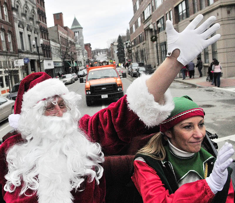 Santa Claus, left, and Jingle the elf wave as they ride down Water Street in a horse-drawn carriage, driven by Cathy Simmons of S&S Carriage Rides, before the annual tree lighting events on Saturday, on Water Street in downtown Augusta.