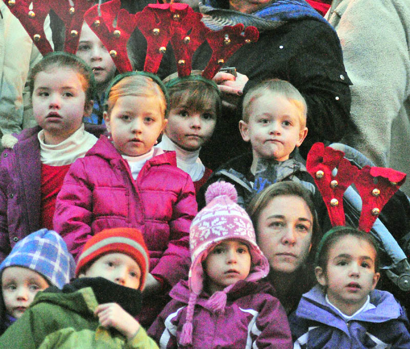 Spectators watch dancers perform in the middle of Water Street, in front of the Olde Federal Building, before the annual tree lighting on Saturday in downtown Augusta. The children wearing antlers were waiting their turn to perform.