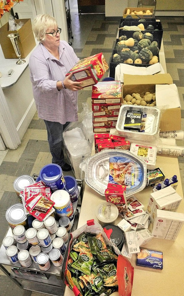 Coordinator Heidi Bowden stacks and organizes food on Wednesday afternoon for annual Thanksgiving community dinner at the Green Street United Methodist Church.