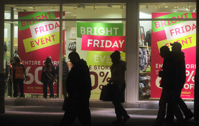 Shoppers walk past a store in the Marketplace at Augusta at 6:06 a.m. on Friday morning in Augusta. Some stores there had opened as early as midnight.
