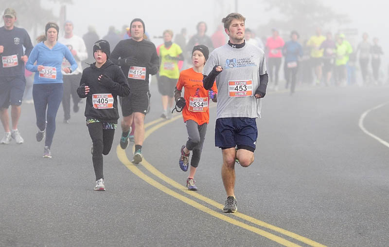 Runners round a bend on Pierce Drive during the Gasping Gobbler 5K race on Thursday morning that started and ended at Cony High School in Augusta. There were over 400 finishers in the annual Thanksgiving day race that gave food for prizes. The first male and female finisher got a trophy and full Thanksgiving dinner. In the each age group, the prizes were a turkey for first place, pie for second place and then dinner rolls for third.
