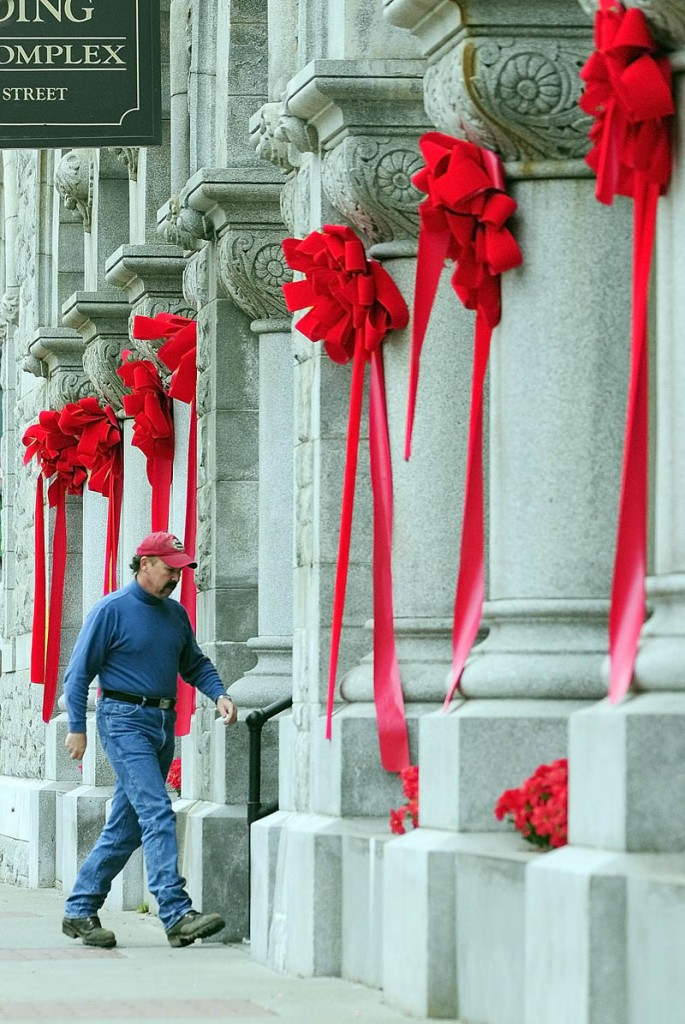 A person walks in the The Olde Federal Building on Wednesday in downtown Augusta. The flowers and red ribbons on the large ornate building at the corner of Water and Winthrop streets were from last weekend's tree lighting events when it was Santa's castle.