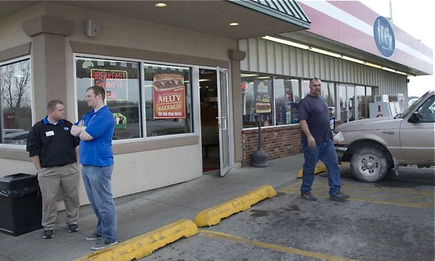 An unidentified customer walks out of the Trex Mart convenience store, right, while manager Chris Nauerz, left, and son of the owner Baron Hartell stand outside, in Dearborn, Mo., on Thursday.