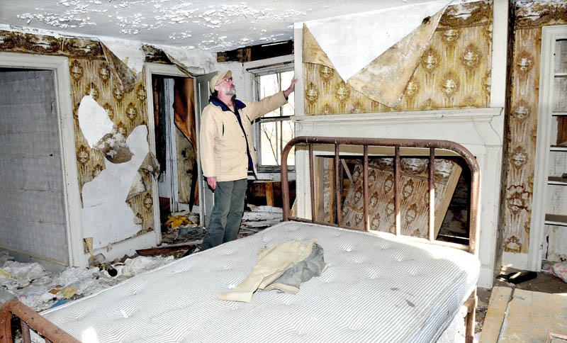 Bob Hubbard examines the hearth around a fireplace in the John Wentworth home, built in 1800 in Athens. The home has not been lived in for decades and may be torn down next year.