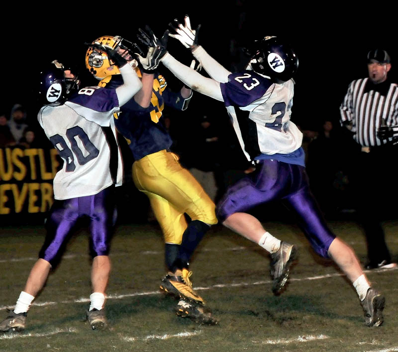 Staff photo by David Leaming Mt. Blue's Nick Hyde reaches for throw as Waterville's Devin Burgess, left, and Jordan DeRosby pressure during game on Friday in Farmington.
