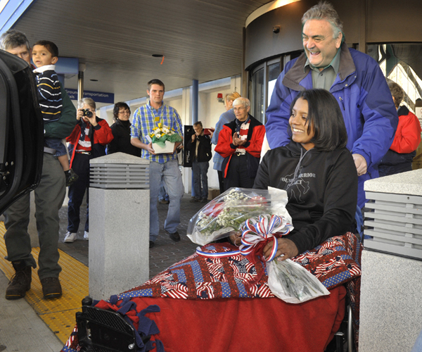 Army Sgt. Helaina Lake, who was severely injured in Afghanistan, returned home to Maine at the Portland Jetport on Tuesday. With assistance from her uncle, Maurice Castonguay, Lake is brought to a limo for the ride home to Livermore Falls.