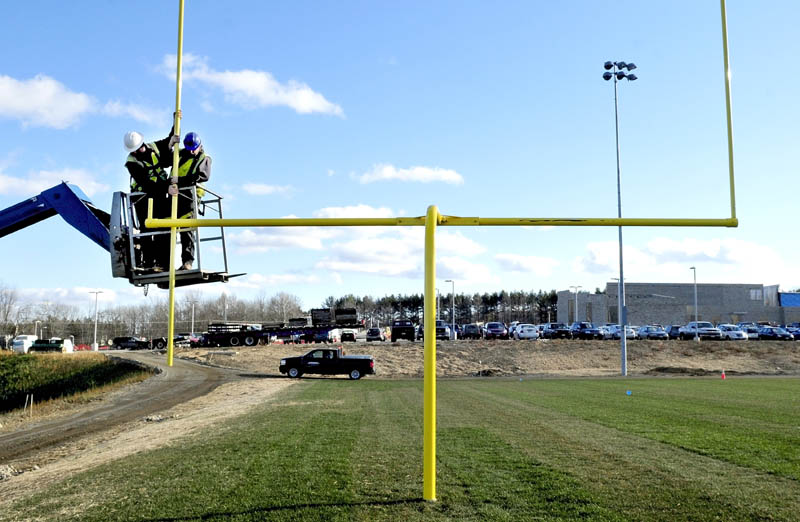 David Durrell, left, and Kermit Clements, of E.L. Vining & Son, work on one of the goalposts at the new football field, at Mt. Blue High School in Farmington, on Monday. Work on the school expansion project and athletic fields is expected to be finished next year.