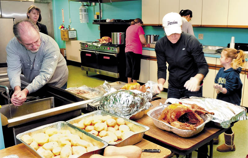 Staff and volunteers with the Skowhegan Community Center on Wednesday pitched in to prepare free Thanksgiving meals to all who stop in between 11 a.m. and 1 p.m. today. From left are John Doucette Jr., Mary Humphrey, Donna McDaniel, Denise Leblanc, Bethanie Sevey, back, and Laney Leblanc.