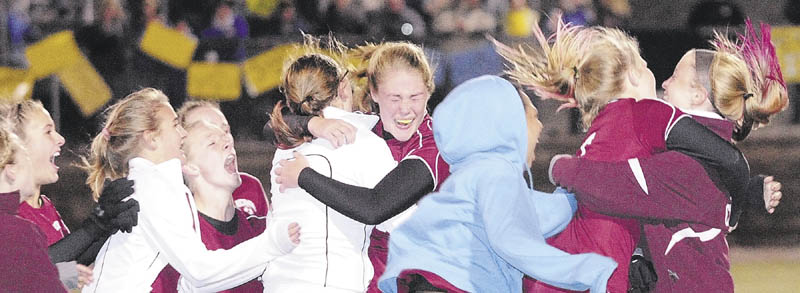 CHAMPIONS: Richmond's Brianna Snedecker, center, is mobbed by her teammates after her penalty kick helped seal a victory over Washburn as the Bobcats won the Class D state championship on Saturday night at Hampden Academy.