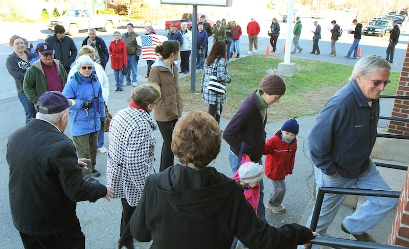 Photo by Jeff Pouland LINING UP TO VOTE: A long line of voters extends out the door of the Bourque-Lanigan American Legion Post 5 shortly after the polls opened in Waterville on Tuesday. High voter turn out is expected today.