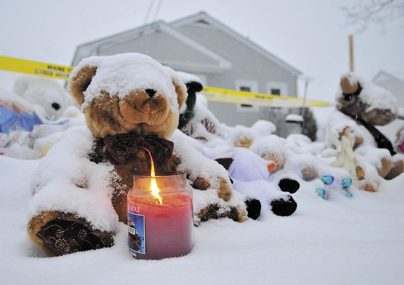 A candle illuminates a growing teddy bear shrine for missing girl Ayla Reynolds outside her home in Waterville on Dec. 25, 2011.