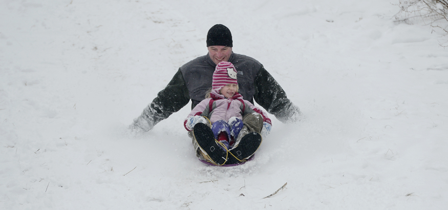 Ryan Guite of South Portland slides down the hill on Eastern Prom in Portland with his daughter Emma, 4, on Monday.