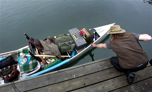Michael Richard Smith steadies his canoe at a wharf in Boston Harbor on Tuesday.