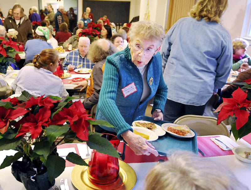 Phyllis Tessman serves pie Tuesday, during a Christmas dinner at Prince of Peace Lutheran Church in Augusta. Several guests ate meals prepared by volunteers at the church.