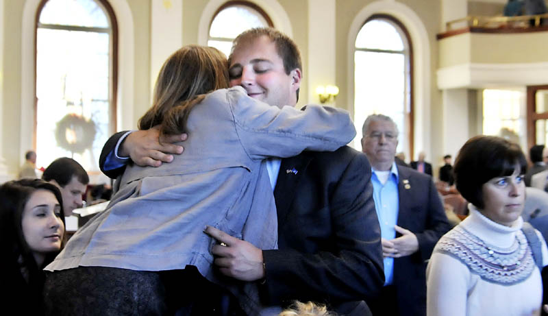 Matt Pouliot, R-Augusta, hugs his mother, Lisa Pouliot, Wednesday, Dec. 5, before taking the oath of office in the House of Representatives in Augusta.