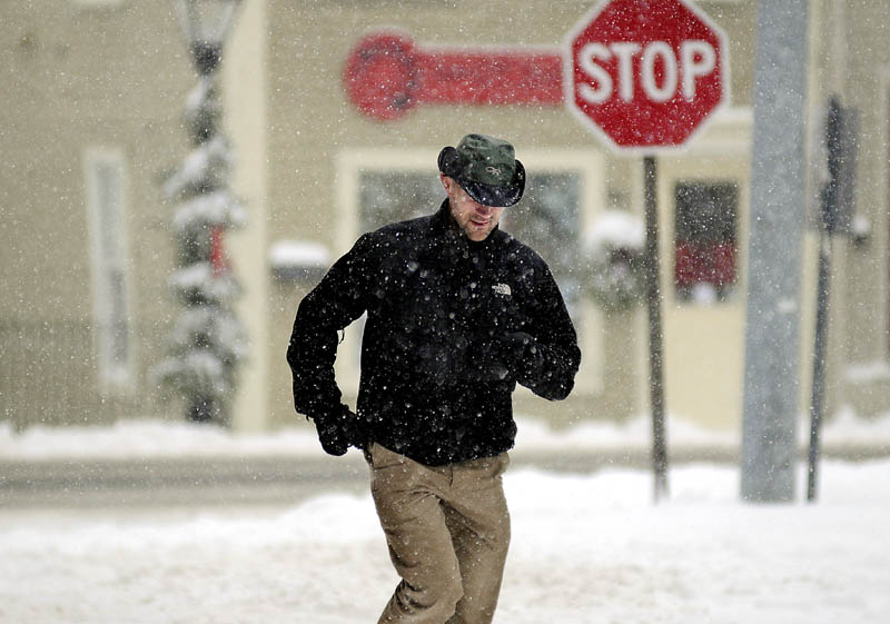 Dr. Nate Murray-James runs back to his Hallowell office on Thursday, after running a quick errand between seeing patients at Hallowell Family Practice. Most offices and schools were closed during the storm that dumped up to a foot of snow across Maine.