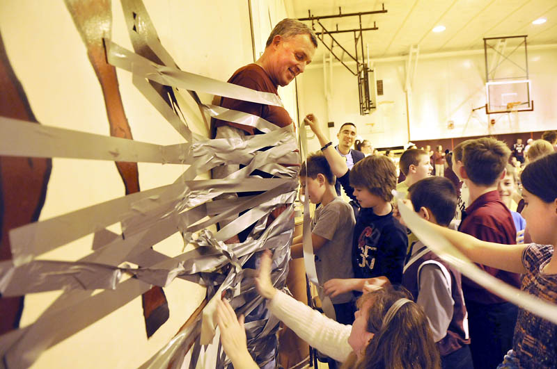 Monmouth Middle School principal Steve Philbrook is taped to a wall in the gym on Monday, during a schoolwide assembly of students and faculty. The students were promised a chance to tape the principal to the wall if they assembled more food items than last year for the annual Cottrell-Taylor food drive. Students from the 4th through 8th grades surpassed last year's collection by gathering 3,454 nonperishable items to donate during the holidays to several area families. After a several rolls of tape were applied, a box beneath Philbrook's feet was removed, and he remained firmly in place until faculty cut him loose.