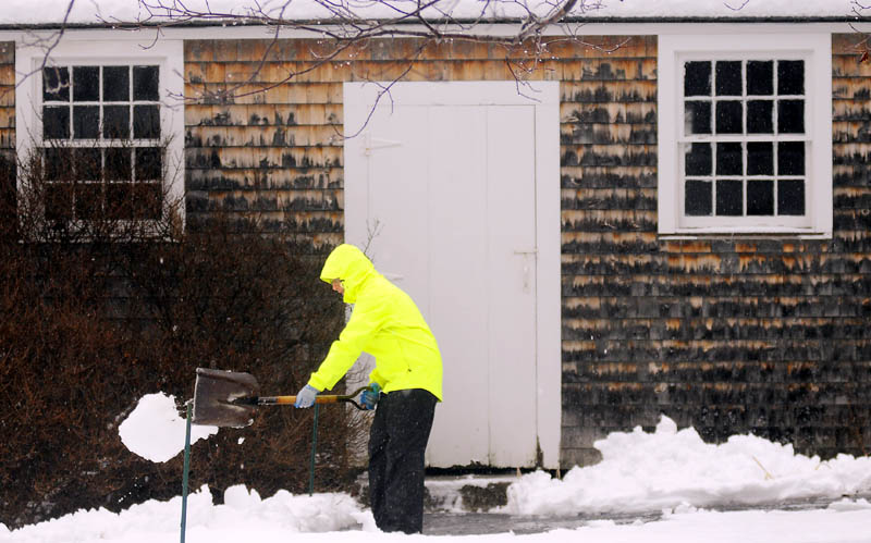 Nancy Russell, of Readfield, moves slush away from the walkway of her shed Tuesday, as rain descends upon the fresh coat of snow.