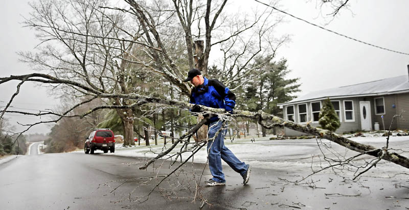 John Smith moves a limb Monday from the lawn of his mother-in-law's Augusta home. Smith said the late fall weather is