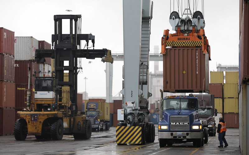 A truck driver watches as a container crane lowers a freight container onto a tractor trailer at the Port of Boston. The crane and a reach stacker, left, are operated by longshoremen at the port. The longshoremen's union has agreed to extend its contract until Feb. 6.