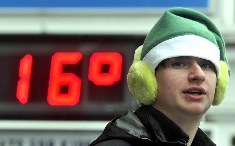 Kegan Blood, 16, of New Sharon, doubles up with the hat and earmuff combo as 16 degrees flashes on the Franklin Savings Bank sign, while tending the hot chocolate table at Franklin Savings Bank on Main Street, during the Chester Greenwood Day parade in downtown Farmington Saturday.