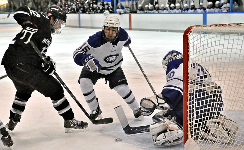 Bowdoin College's Harry Matheson, 12, left, takes a shot on Colby College goalie Jordan Nathan, 30, right, as Jack Bartlett, 15, center, defends in the first period at Alfond Arena at Colby College in Waterville on Saturday.