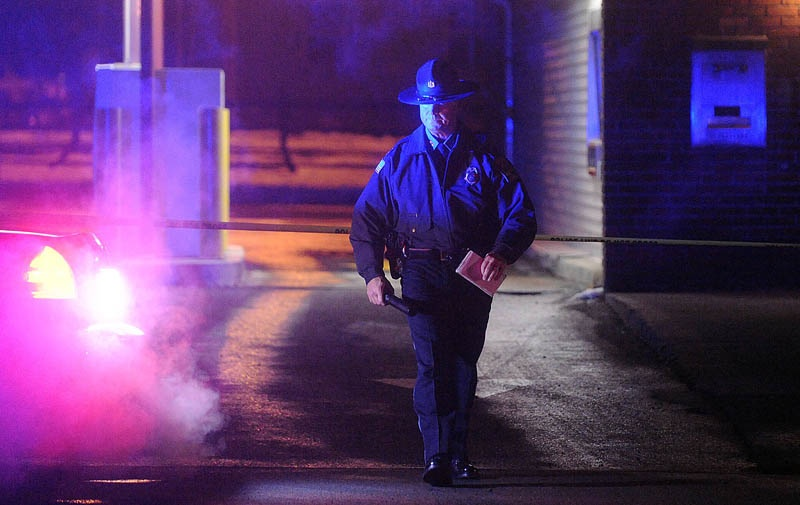 Michael Emmons, Skowhegan police chief, emerges from the drive-through teller bay at Franklin Savings Bank on Madison Avenue in Skowhegan Thursday, Dec. 13, 2012, while investigating a robbery.