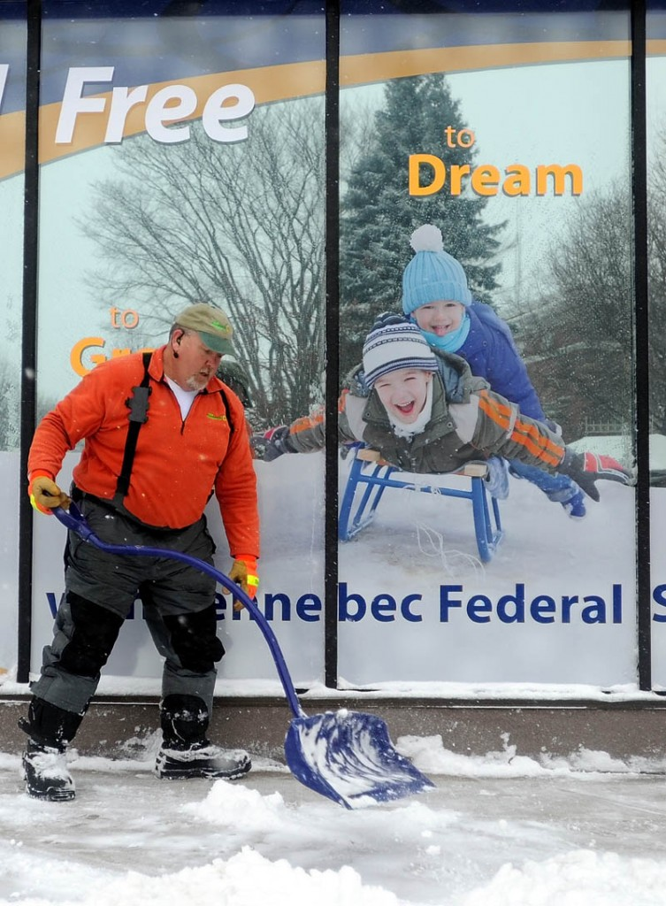Bruce Heath, owner of KB Property Care, clears the sidewalk in front of Kennebec Federal Savings Bank on Main Street in downtown Waterville on Thursday.