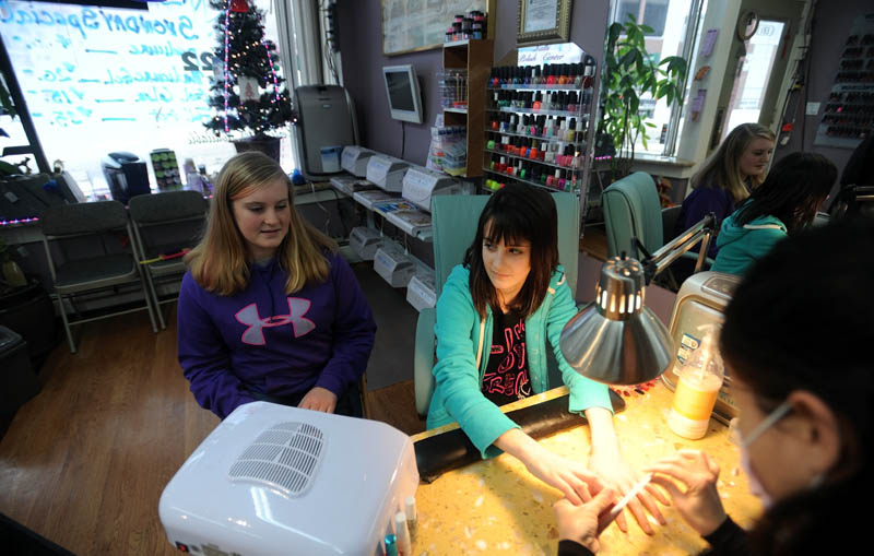 Kaitlin Blair, 13, center, and Madison Klowes, 13, left, get their nails done by Brandy Pham, 40, right, at DK Nails on Main Street in Waterville on Thursday. DK Nails was offering a special snow sale to help boost sales.