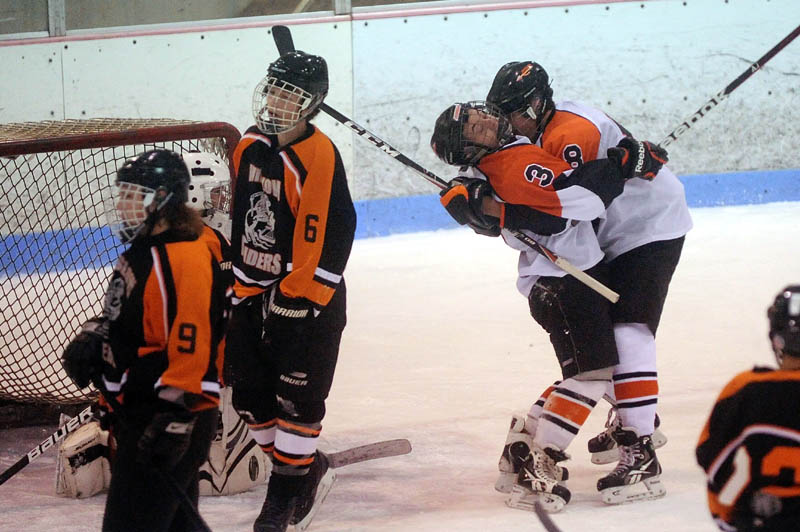 CELEBRATE: Skowhegan High School teammates Kyle Demchak, 3, and Chase Nelson, 8, celebrate Demchak's goal in the first period at Sukee Arena in Winslow on Wednesday.
