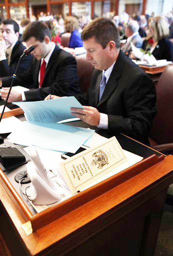 House Minority Leader Rep. Kenneth Fredette, of Newport, looks over papers after being sworn in for his second term on Wednesday at the State House.